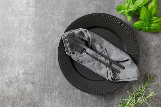 ハーブとダークストーンのテーブルに黒いプレート、カトラリー、キッチンタオルでテーブルセッティング