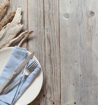 青いナプキンと古い木でテーブルセッティング