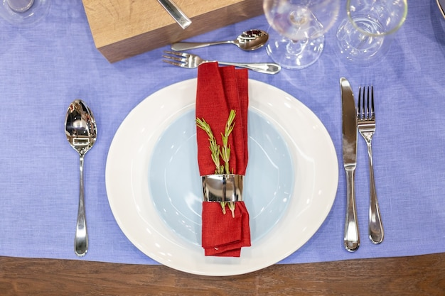Table setting with a blue tablecloth, a white and blue plate, a red napkin in a steel holder, steel appliances, glass goblets. top view, close up