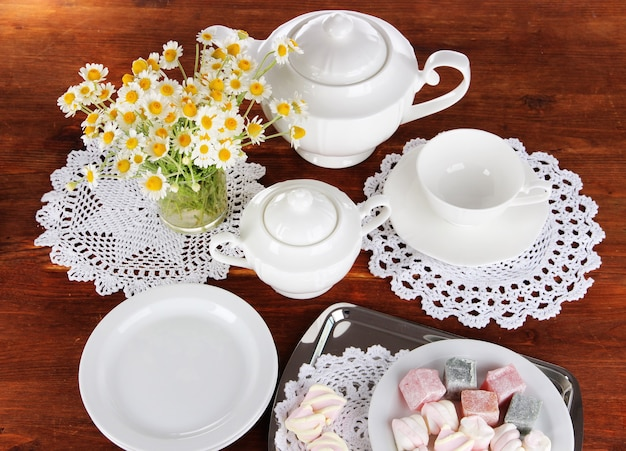 Table setting with chamomiles on wooden table