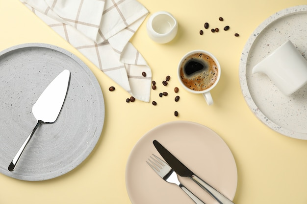 Table setting with cup of coffee on beige background, top view
