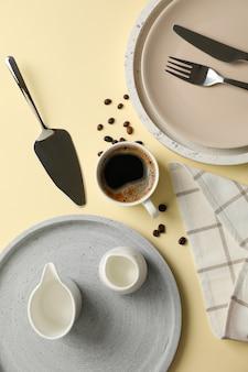 Сервировка стола с чашкой кофе на бежевом фоне, вид сверху