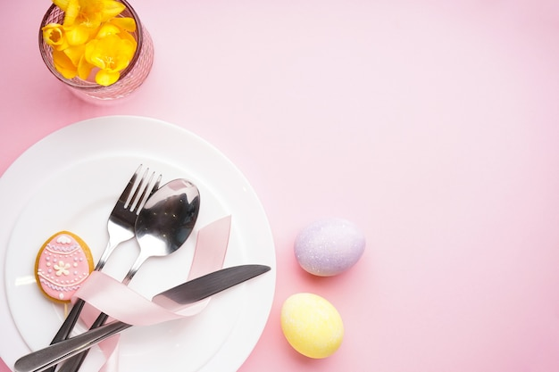 Сервировка стола со столовыми приборами и пасхальными украшениями на розовом столе. вид сверху, место для текста.