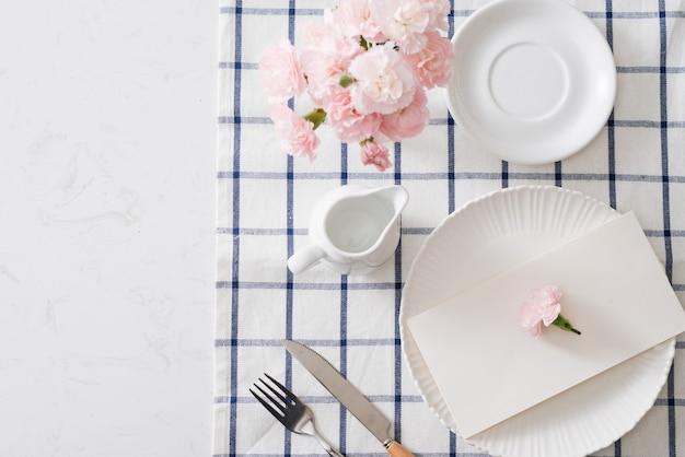 흰색 배경에 접시, 칼 붙이, 꽃이 있는 테이블 설정