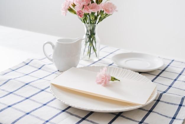 白い背景の上の皿、カトラリー、花とテーブルの設定