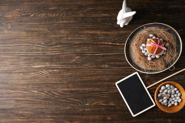 Сервировка стола с пасхальными украшениями на деревянном столе. вид сверху, место для текста.