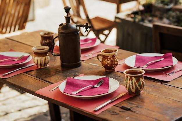 空のプレートと木製の背景にカトラリーとテーブルの設定
