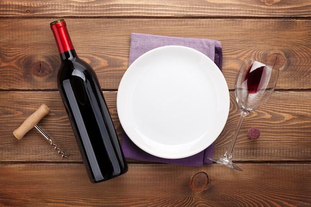 빈 접시, 와인 잔, 레드 와인 병이 있는 테이블 설정. 소박한 나무 테이블 배경 위에 위에서 보기