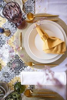 Сервировка стола с цветами белая тарелка и вид сверху столовых приборов