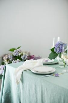 Сервировка стола керамическими тарелками ручной работы на зеленой льняной скатерти и цветы. концепция партии