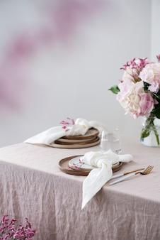Сервировка стола керамическими тарелками ручной работы на льняной скатерти и цветы. концепция партии