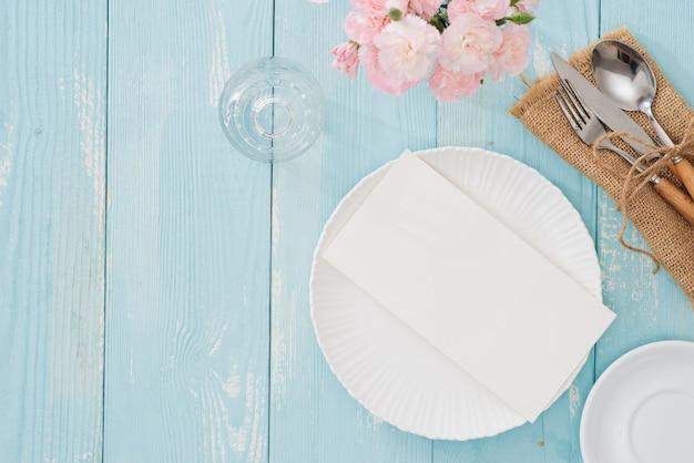 나무 배경에 접시, 포크, 나이프가 있는 테이블 설정