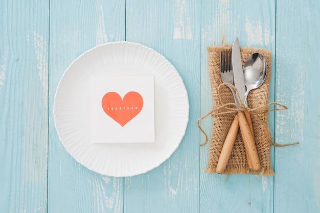 木製の背景にプレート、フォーク、ナイフとテーブルの設定