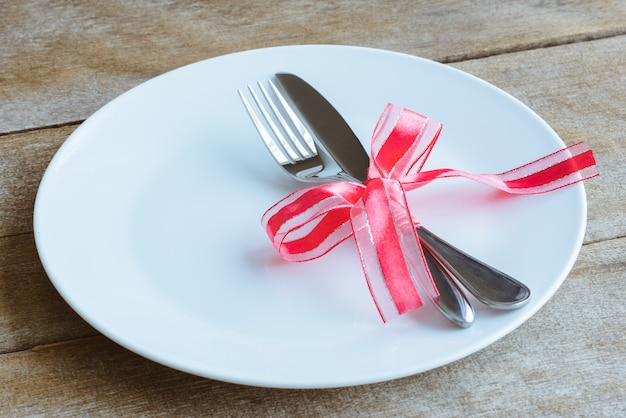 Table setting with plate, knife, fork, red ribbon and hearts on wooden table