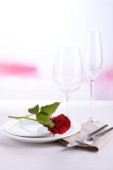 プレートに赤いバラのテーブルセッティング
