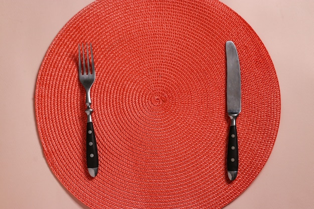 Table setting with a round wicker napkin of orange color, a fork and a knife, for one person, top view
