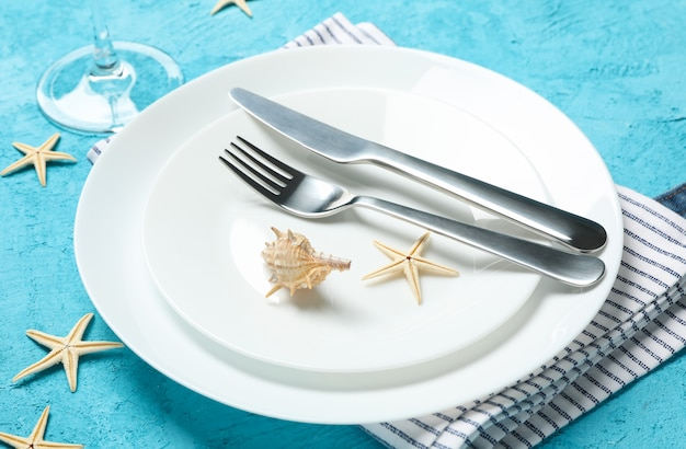 Table setting with seashells and starfishes on turquoise surface