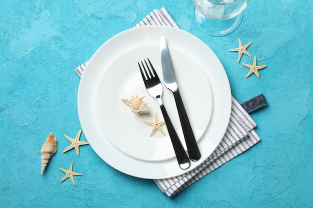 Table setting with seashells and starfishes on turquoise, top view