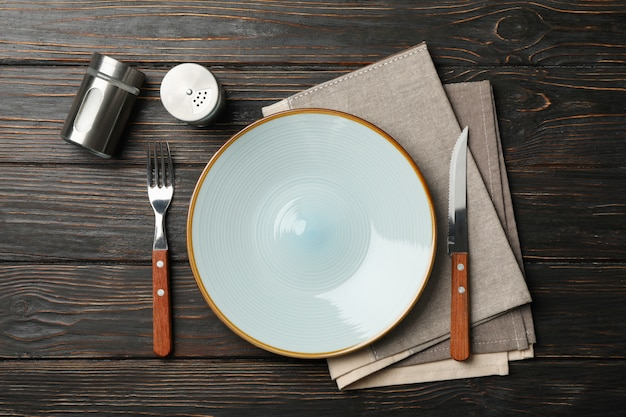 Table setting with spices and towel on wooden background, top view