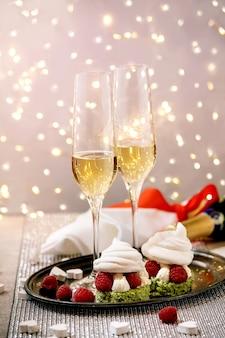 Сервировка стола с двумя бокалами шампанского и десертами из ягодного безе на подносе, стоящем на серебряном игристом столе, белые сердца, огни боке