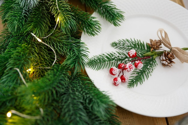 식기가 있는 테이블 세팅 축제 장식 전나무 가지와 화환