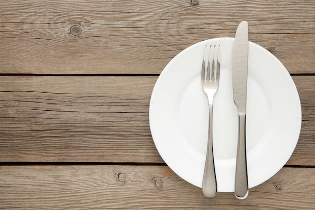 Сервировка стола с белыми тарелками и столовыми приборами