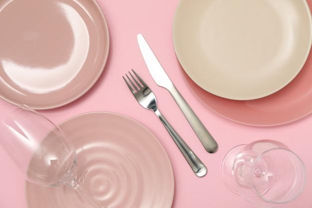 ピンクの背景、上面に使い捨てからすを持つテーブルの設定