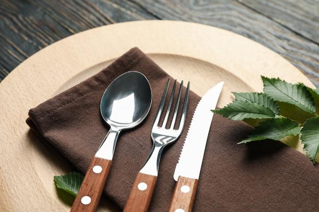 Сервировка стола с деревянной тарелкой и столовыми приборами на деревянном