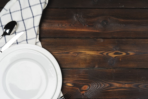 Table setup with plates on dark wooden wall