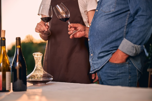 Table in sunset light with bottles and wine decanter. two unrecognized men clanging glasses