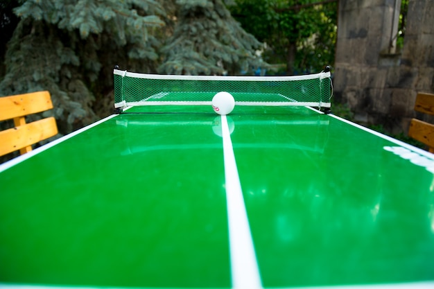 Игра в настольный теннис и мяч на зеленой теннисной доске