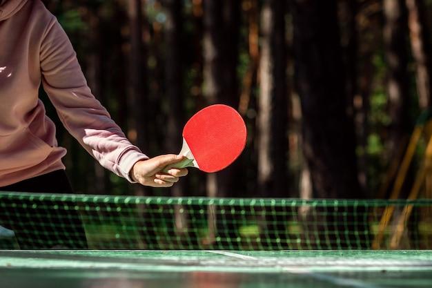 Игрок в настольный теннис делает подачу, крупный план
