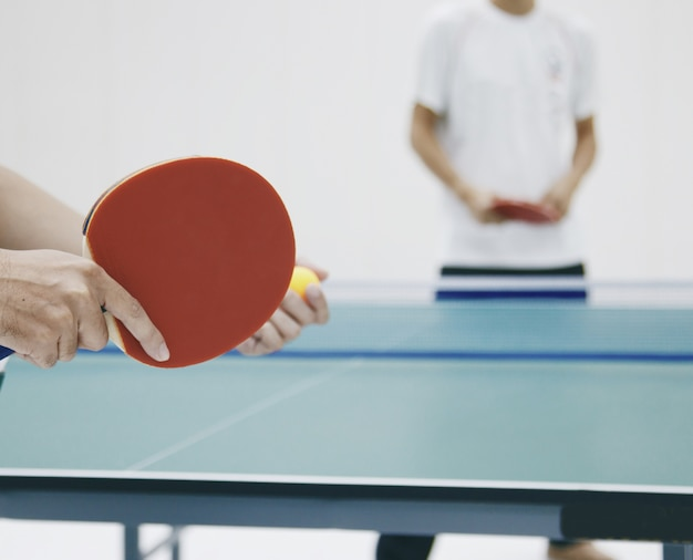 Table tennis players preparing to hit the ball competitors stand waiting.