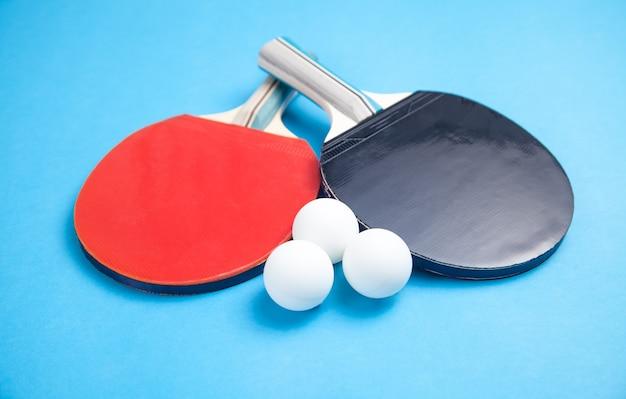 卓球のラケットと青い背景の上の白いプラスチックボール。