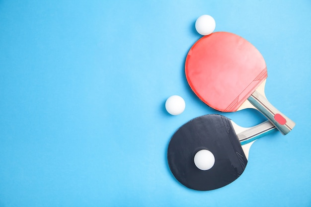 Table tennis rackets and a white plastic balls on blue, flat lay