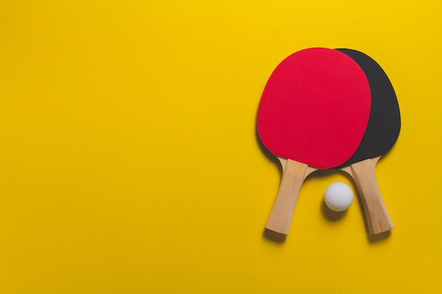 Table tennis rackets on yellow surface