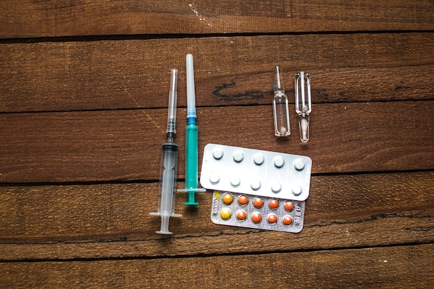 On the table there are ampoules, next different pills,drugs and medications