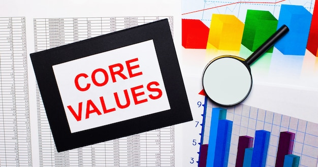 On the table there are reports of multi-colored charts, a magnifying glass and a sheet of paper in a black frame with the text core values. business concept