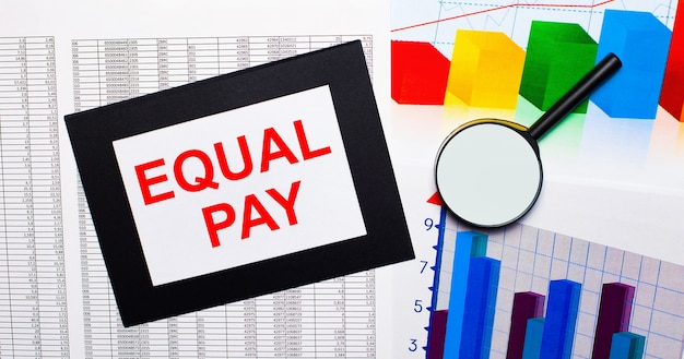 On the table there are reports of multi-colored charts, a magnifying glass and a sheet of paper in a black frame with the text equal pay. business concept