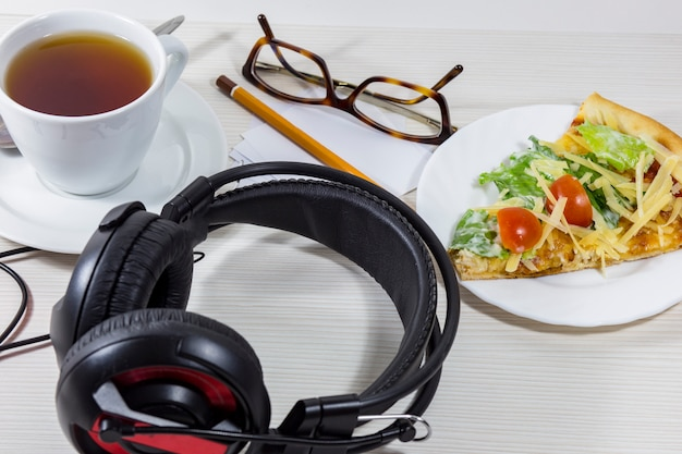 On the table there is a cup of tea, a piece of pizza, headphones and a pencil, a sheet of paper and glasses