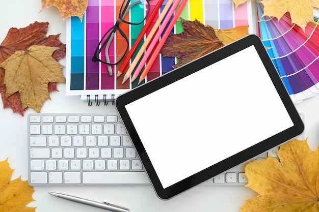 On table there is a keyboard with tablet glasses autumn leaves and colored polish.