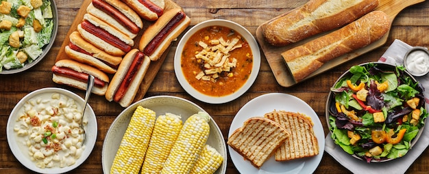 Настольное блюдо с хот-догами, жареным сыром, супом и салатом в плоской композиции