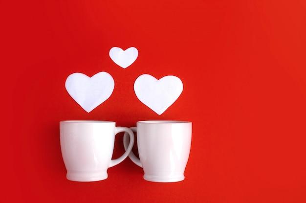 テーブルトップビューサインバレンタインデーの背景概念の空中画像。フラットレイアウト配置ホームオフィスデスクスタジオでモダンなピンクの紙にスチームハート形の白いコーヒーカップ。パステルトーンデザイン。