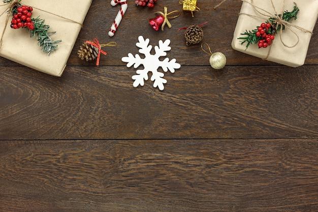 メリークリスマス&ハッピーニューイヤーコンセプト背景のテーブルトップビュー。現代的な茶色の木材に必須のお祝いの飾り。創造的なテキストや言葉遣いのためのスペースをコピーします。デザインモックアップとテンプレート。