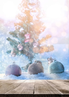 Table top with fantasy chrismas ball on snow with chrismas tree abstract background.