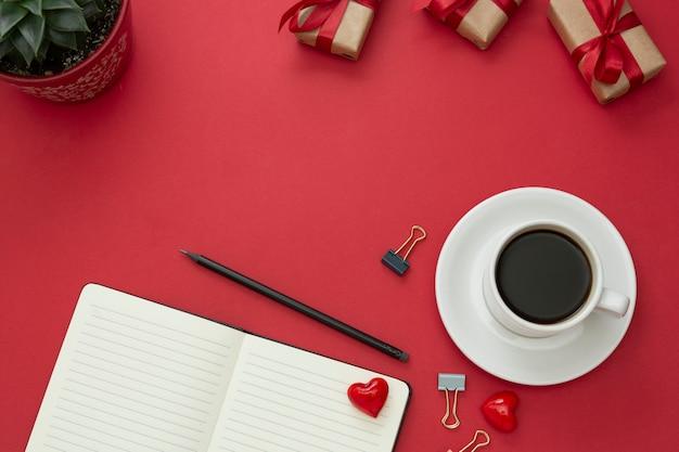 テーブルトップ、開いているノートブックと赤の背景にコーヒーカップのワーキングデスク。テキスト用のスペースをコピーします。