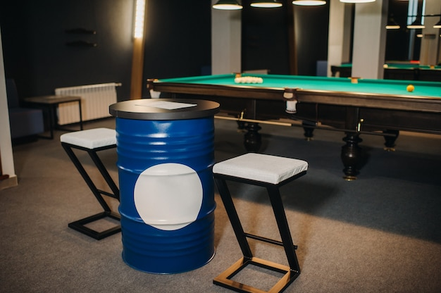 Table and two chairs near the green-covered billiard table with balls in the billiard club.