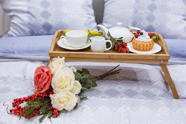 Столик с чашкой и цветком на кровати, кофе в постели утром