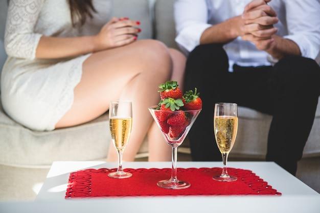 Стол со стаканом с клубникой и два бокала шампанского