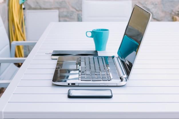 Стол с ноутбуком, телефоном, блокнотом и чашкой для удаленной работы в саду своего дома.